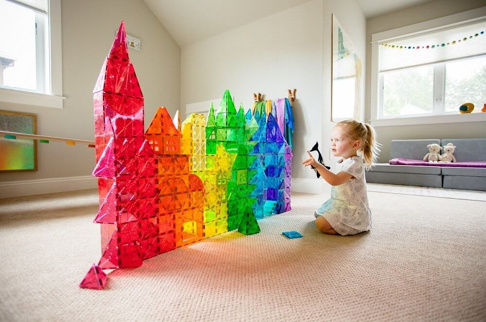 Little girl building a fortress out of Magna-Tiles