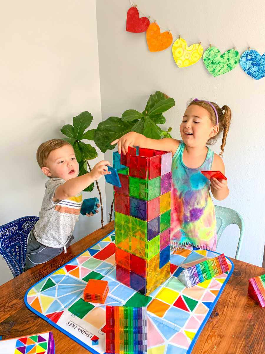 A little boy and girl building with Magna-Tiles
